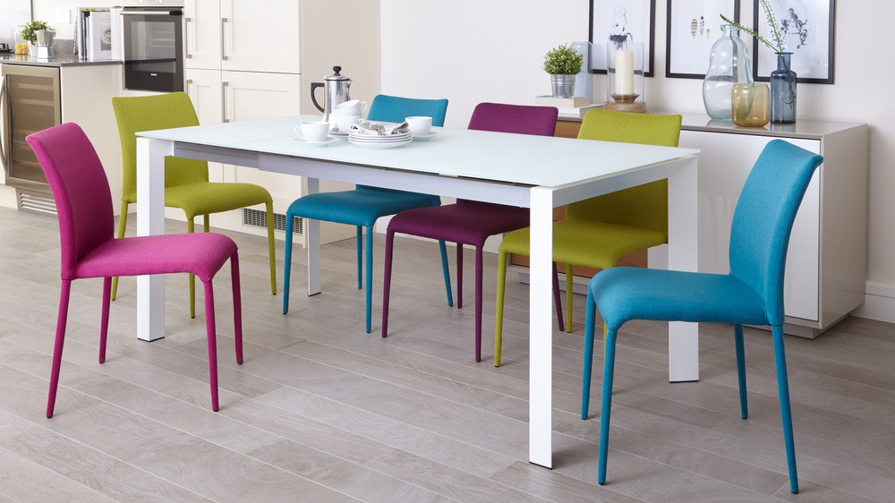 White frosted glass modern extending table and colourful fabric chairs