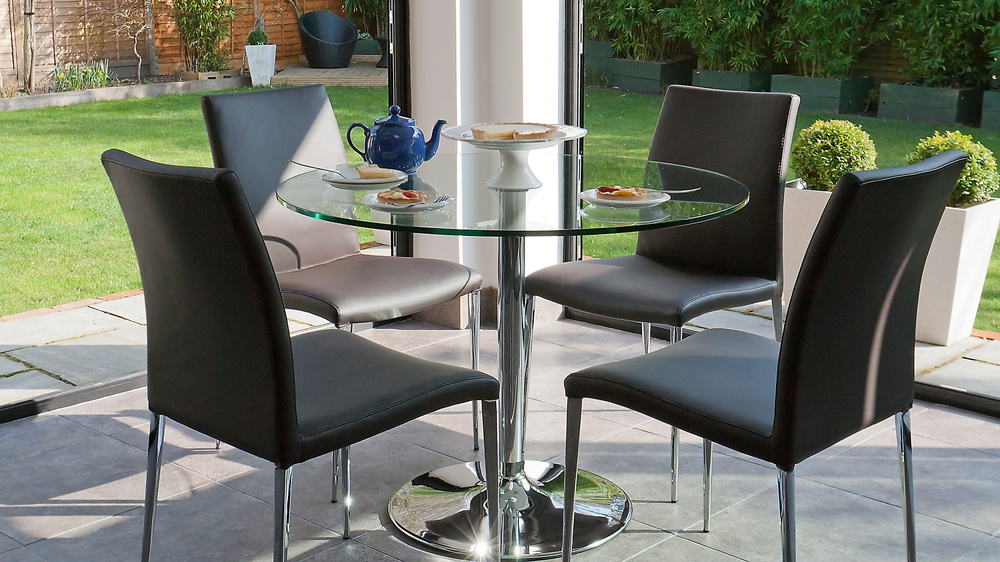 contemporary chrome pedestal dining table with a round glass table top